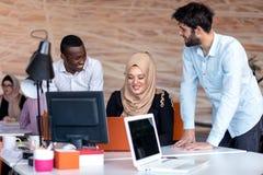 在会议的起始的企业队在现代明亮的办公室内部激发灵感、工作在膝上型计算机和片剂计算机 库存照片
