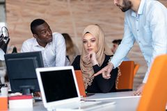 在会议的起始的企业队在现代明亮的办公室内部激发灵感、工作在膝上型计算机和片剂计算机 免版税库存图片