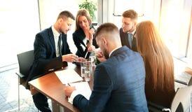 在会议的起始的企业队在现代明亮的办公室内部激发灵感、工作在膝上型计算机和片剂计算机 库存图片