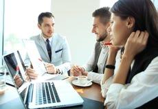 在会议的起始的企业队在现代明亮的办公室内部激发灵感、工作在膝上型计算机和片剂计算机 免版税库存照片