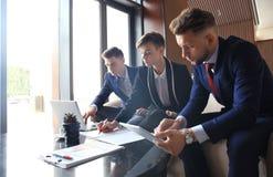 在会议的起始的企业队在现代明亮的办公室内部激发灵感、工作在膝上型计算机和片剂计算机 免版税图库摄影
