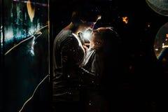 在伞亲吻下的年轻夫妇在城市街道上的晚上 免版税图库摄影