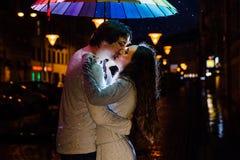 在伞亲吻下的年轻夫妇在城市街道上的晚上 免版税库存照片
