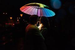 在伞亲吻下的年轻夫妇在城市街道上的晚上 库存照片