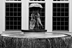 在伞喷泉下的两个孩子 免版税库存图片