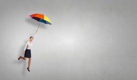 在伞的妇女飞行 免版税库存图片