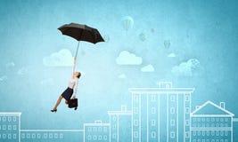 在伞的妇女飞行 免版税库存照片