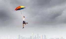 在伞的妇女飞行 图库摄影