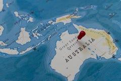 在伟大的含沙沙漠,世界地图的澳大利亚的一个别针 免版税库存图片
