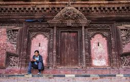 在传统尼泊尔寺庙附近墙壁供以人员坐 免版税库存照片