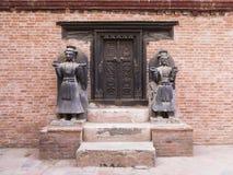 在传统尼泊尔样式的富有地被雕刻的黑暗的木门与两个美丽的与实物大小一样的雕象 库存照片