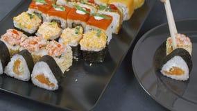 在传统日本空的正方形黑色板岩板材的顶视图构筑用寿司,姜,大豆,山葵碗,绿色 影视素材