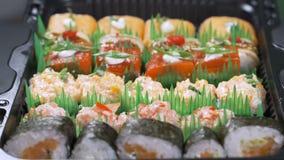 在传统日本空的正方形黑色板岩板材的顶视图构筑用寿司,姜,大豆,山葵碗,绿色 股票视频