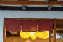 在传统日本餐馆前面垂悬的象帷幕的织品 图库摄影