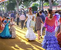 在传统服装散步和打扮的可爱的妇女在塞维利亚` s 4月市场 库存图片