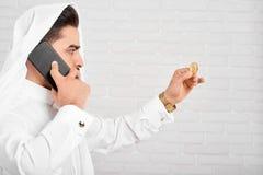 在传统服装的一个阿拉伯商人在金黄bitcoin看 库存图片