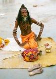 在传统礼服的印度希瓦sadhu坐您的在恒河的银行的席子 免版税库存图片
