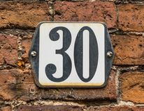 在传统荷兰砖墙上的房子号码30 图库摄影