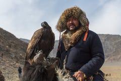 在传统衣物的老鹰猎人,有在他的胳膊的一只鹫的在与鸟的每年全国竞争时 库存照片