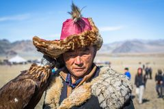 在传统衣物的老鹰猎人,有在他的胳膊的一只鹫的在与鸷的每年全国竞争时BERKUTC 免版税库存图片