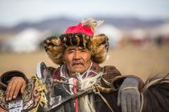 在传统衣物的老鹰猎人,有在他的胳膊的一只鹫的 图库摄影