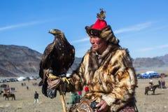 在传统衣物的老鹰猎人,有在他的胳膊的一只鹫的 库存照片