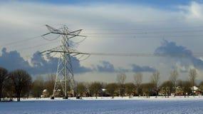 在传输塔后的雪盖的镇的看法 免版税库存图片
