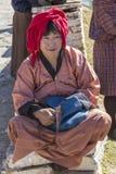 在传统不丹人打扮的妇女等待公共汽车 库存图片