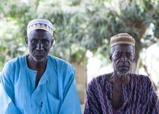 在传统五颜六色的衣裳和回教盖帽的非洲村庄长辈 免版税库存照片