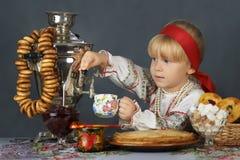 在传统俄国sarafan和衬衣的小女孩饮用的茶 免版税库存图片
