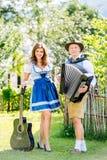 在传统巴法力亚衣裳的夫妇有吉他和手风琴的 免版税库存图片