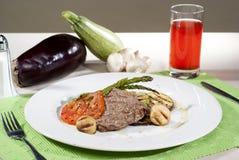 在传统调味汁沐浴的阿根廷肉块服务与菜 免版税图库摄影