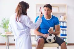 在伤害以后的橄榄球足球运动员参观的医生 图库摄影