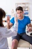 在伤害以后的橄榄球足球运动员参观的医生 库存图片