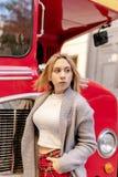 在伦敦红色公共汽车附近的年轻女人身分 免版税库存图片