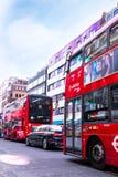 在伦敦-有广告和黑默西迪丝的两辆典型的红色公共汽车交易,站立在交通 免版税库存图片