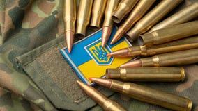 在伪装军事夹克和作战子弹背景的乌克兰旗子  国家防御概念 库存图片