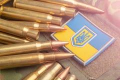 在伪装军用夹克和作战子弹的背景的乌克兰旗子 国家防御概念 库存图片