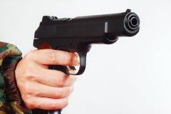 在伪装制服的手有一把半自动军队手枪的 库存照片