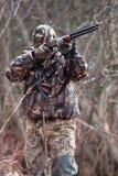 在伪装射击的猎人从枪 免版税库存照片
