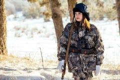 在伪装的女性猎人给准备好寻找穿衣,拿着枪a 免版税库存照片