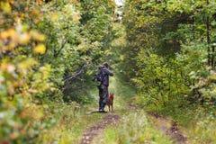 在伪装的猎人与在森林公路的狗 免版税库存照片
