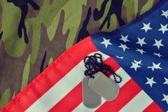 在伪装织品的美国国旗和战士徽章 库存照片