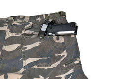 在伪装裤兜白色后面的1911年半自动手枪 免版税库存照片