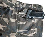 在伪装裤兜白色后面的1911年半自动手枪 库存图片