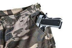 在伪装裤兜白色后面的1911年半自动手枪 免版税库存图片