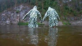 在伪装雨衣的滑稽的导电线 两个少年在雨中进行同步的舞蹈移动,站立knee-deep  影视素材
