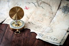 在伪造品前面的船舶指南针盗版在木桌上的珍宝地图 图库摄影