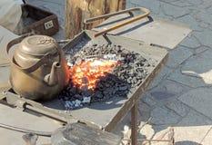 在伪造火的古老的水壶 免版税库存照片