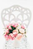 在伪造的葡萄酒椅子的美丽的花束牡丹在绝尘室 免版税库存图片